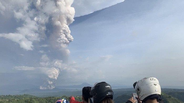 Warga memotret erupsi Gunung Taal di wilayah Cavite, Filipina, Minggu sore pukul 17.30 (12/1/2020).