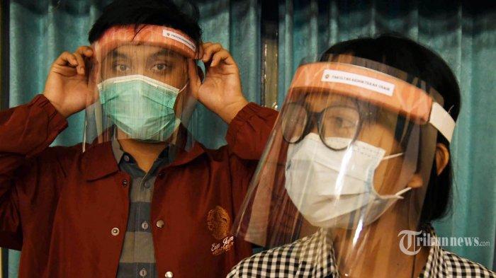 FACE SHIELD SEDERHANA - Dua mahasiswa mencoba face shield sederhana buatan mahasiswa Fakultas Kedokteran Universitas Airlangga di sela tugas kuliah onlinenya di aula FK Unair,  Senin (23/3/2020). Rencananya face shield ini akan dibagikan ke RS Unair dan RSU dr Soetomo karena di dua rumah sakit itu sebagai pusat rujukan pasien Covid-19.  (SURYA/AHMAD ZAIMUL HAQ)