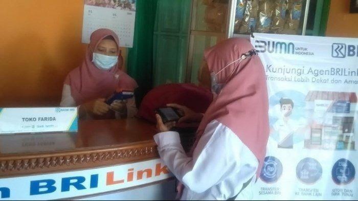 Farida (kiri) sedang melayani transaksi transfer pelanggannya di Toko Farida di Desa Patereman, Kecamatan Modung, Kabupaten Bangkalan, Jawa Timur, Rabu (9/6/2021). Toko Farida merupakan salah satu unit link BRILink Bangkalan