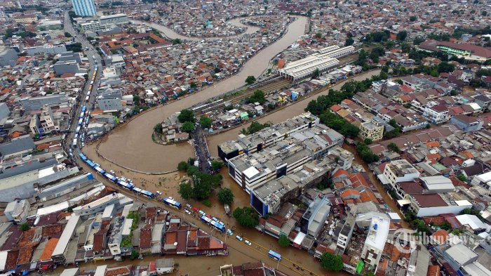 Sejumlah kendaraan mencoba menerobos banjir yang menggenangi Jalan Jatinegara Barat dan sekitarnya, di Jakarta Timur, Rabu (1/1/2020). Curah hujan yang tinggi ditambah dengan luapan air Sungai Ciliwung dan tingginya muka air laut membuat beberapa kawasan di Jakarta terendam banjir. Warta Kota/Alex Suban