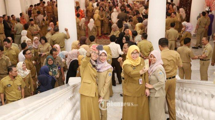 Sejumlah Pegawai Negeri Sipil (PNS) saat berselfie ditengah kerumunan pegawai saat acara halal bihalal dengan sejumlah Pegawai Negeri Sipil (PNS) di Gedung Balaikota, Jakarta Pusat, Senin (10/6/2019). Acara tersebut diikuti oleh ratusan pegaiwai balaikota Jakarta.(Tribunnews/Jeprima)