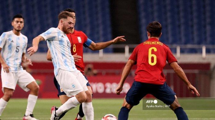 Gelandang Argentina Alexis Mac Allister (kedua dari kiri) menendang bola di antara gelandang Spanyol Mikel Merino (kedua dari kanan) dan gelandang Martin Zubimendi (kanan) selama pertandingan sepak bola putaran pertama grup C putra Olimpiade Tokyo 2020 antara Spanyol dan Argentina di Stadion Saitama di Saitama pada 28 Juli 2021.