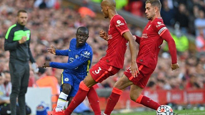 Gelandang Chelsea asal Prancis N'Golo Kante (kiri) mengoper bola melewati pemain tengah Liverpool asal Brasil Fabinho dan pemain tengah Liverpool asal Inggris Jordan Henderson (kanan) selama pertandingan sepak bola Liga Utama Inggris antara Liverpool dan Chelsea di Anfield di Liverpool, barat laut Inggris pada 28 Agustus, 2021. Paul ELLIS / AFP