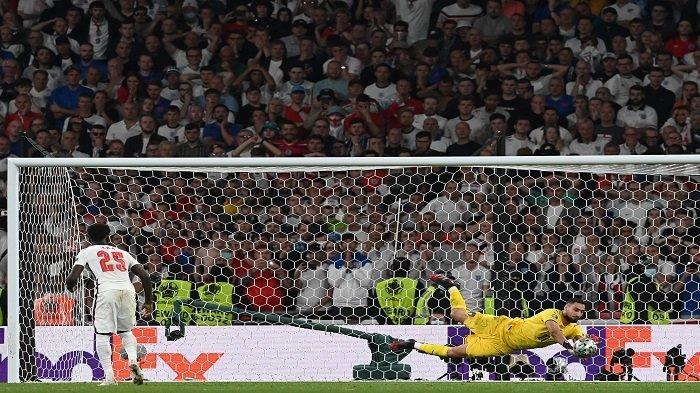 Penjaga gawang Italia Gianluigi Donnarumma menyelamatkan penalti oleh gelandang Inggris Bukayo Saka dalam adu penalti selama pertandingan sepak bola final UEFA EURO 2020 antara Italia dan Inggris di Stadion Wembley di London pada 11 Juli 2021.