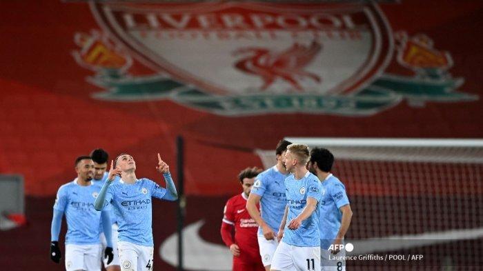 Gelandang Inggris Manchester City Phil Foden (kiri) melakukan selebrasi setelah dia mencetak gol keempat mereka selama pertandingan sepak bola Liga Utama Inggris antara Liverpool dan Manchester City di Anfield di Liverpool, Inggris barat laut pada 7 Februari 2021. LAURENCE GRIFFITHS / POOL / AFP
