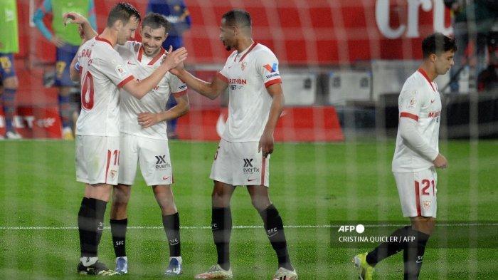 Gelandang <a href='https://manado.tribunnews.com/tag/sevilla' title='Sevilla'>Sevilla</a> Kroasia Ivan Rakitic (kiri) merayakan bersama rekan satu timnya setelah mencetak gol selama pertandingan sepak bola leg pertama semifinal Copa del Rey (Piala Raja) Spanyol antara <a href='https://manado.tribunnews.com/tag/sevilla' title='Sevilla'>Sevilla</a> dan <a href='https://manado.tribunnews.com/tag/barcelona' title='Barcelona'>Barcelona</a> di stadion Ramon Sanchez Pizjuan di Seville pada 10 Februari 2021. CRISTINA QUICLER / AFP