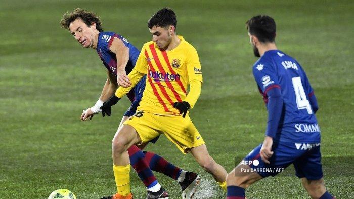 Gelandang <a href='https://manado.tribunnews.com/tag/spanyol' title='Spanyol'>Spanyol</a> Barcelona Pedri (tengah) menantang gelandang <a href='https://manado.tribunnews.com/tag/spanyol' title='Spanyol'>Spanyol</a> Huesca Pedro Mosquera selama pertandingan sepak bola Liga <a href='https://manado.tribunnews.com/tag/spanyol' title='Spanyol'>Spanyol</a> antara Huesca dan Barcelona di stadion El Alcoraz di Huesca pada 3 Januari 2021. Pau BARRENA / AFP