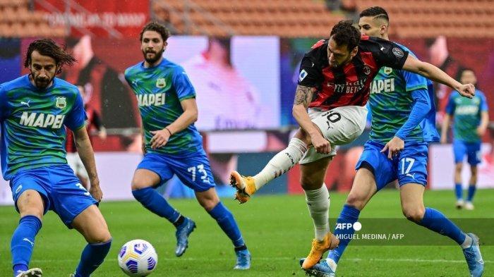 Gelandang Turki AC Milan Hakan Calhanoglu (Depan kanan) menembak tepat sasaran selama pertandingan sepak bola Serie A Italia AC Milan vs Sassuolo pada 21 April 2021 di stadion San Siro di Milan. MIGUEL MEDINA / AFP