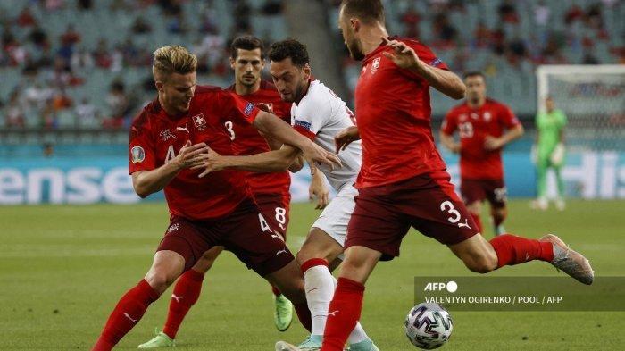 Gelandang Turki Hakan Calhanoglu (tengah) dan bek Swiss Nico Elvedi (kiri) berebut bola pada pertandingan sepak bola Grup A UEFA EURO 2020 antara Swiss dan Turki di Stadion Olimpiade di Baku pada 20 Juni 2021.