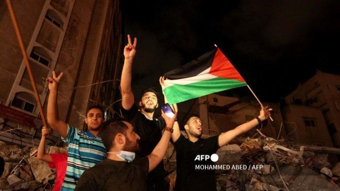 Seorang pria mengibarkan bendera Palestina ketika yang lain mengibarkan tanda V untuk kemenangan saat mereka merayakan gencatan senjata yang ditengahi oleh Mesir antara Israel dan dua kelompok bersenjata utama Palestina di Gaza pada 20 Mei 2021.