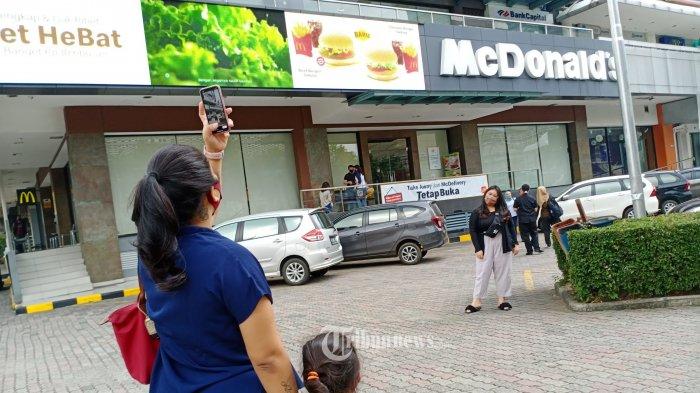 MC DONALS TUTUP - Pelanggan sedang berfoto di depan Gerai MC Donals yang berada di gedung Sarinah, Jalan MH Thamrin, Jakarta Pusat, Kamis (8/5/2020). Gerai resto siap saji yang telah buka  24 jam selama 30 tahun ini akan tutup pada tanggal 10 Mei 2020. WARTA KOTA/HENRY LOPULALAN