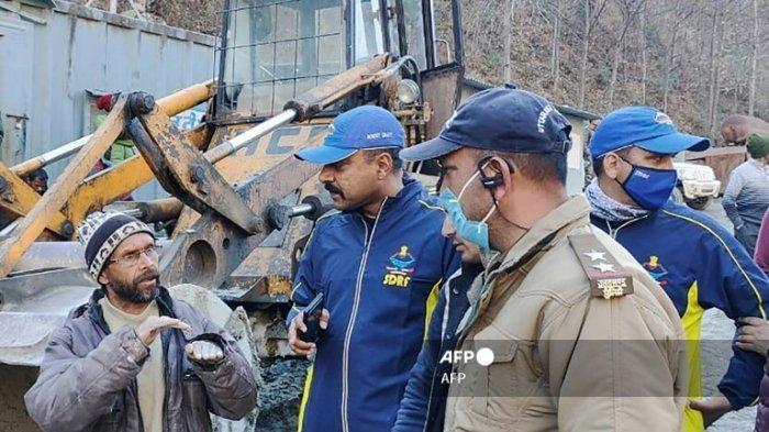 Seorang pekerja berbicara dengan personel State Disaster Response Fund (SDRF) setelah gletser yang rusak menyebabkan gelombang sungai besar yang menyapu jembatan dan jalan, di desa Reni di distrik Chamoli di Uttarakhand pada 7 Februari 2021.