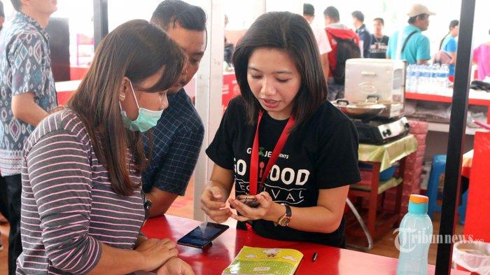 Warga sedang menukarkan uang tunai dengan saldo GoPay di stand gojek yang tersedia pada GoFood Festival, Sabtu (25/8).  (TRIBUN MANADO/ANDREAS RUAUW)