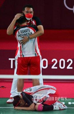 Apriyani Rahayu dari Indonesia dan Greysia Polii dari Indonesia (bawah) merayakan dengan seorang pelatih setelah memenangkan pertandingan final bulu tangkis ganda putri melawan Jia Yifan dari China dan Chen Qingchen dari China selama Olimpiade Tokyo 2020 di Musashino Forest Sports Plaza di Tokyo. Senin (2 Agustus 2021). (Pedro PARDO/AFP)