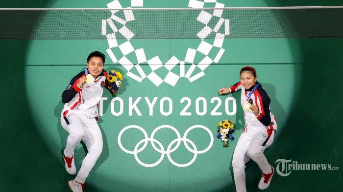 Atlet Indonesia Apriyani Rahayu (kiri) dan Greysia Polii Indonesia berpose di lapangan dengan medali emas bulu tangkis ganda putri mereka selama Olimpiade Tokyo 2020 di Musashino Forest Sports Plaza di Tokyo. Senin (2 Agustus 2021). (LINTAO ZHANG/ POOL/AFP)