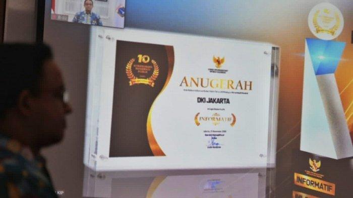 Gubernur DKI Jakarta Anies Baswedan menunjukan penghargaan yang diterima Pemprov DKI Jakarta sebagai Pemda Berkualifikasi Informatif.