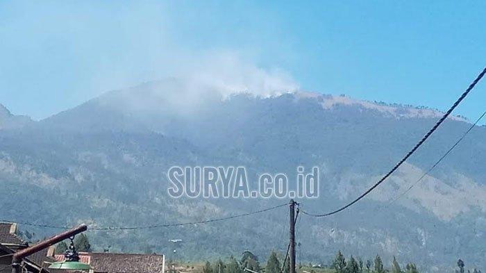 Asap terlihat mengepul dari Gunung Arjuno yang terbakar, Minggu (28/7/2019).