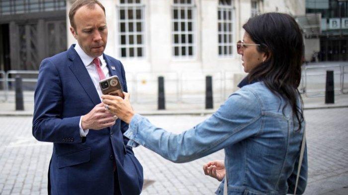 Menteri Kesehatan Inggris Matt Hancock (kiri), melihat telepon ajudannya Gina Coladangelo ketika mereka meninggalkan BBC di pusat kota London pada 6 Juni 2021.