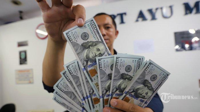 Pegawai menunjukan uang dolar Amerika Serikat di gerai penukaran uang Ayu Masagung di Jalan Kramat Kwitang, Senen, Jakarta Pusat, Kamis (19/3/2020). Nilai tukar rupiah terus tertekan sejak beberapa pekan terakhir, terutama setelah merebaknya wabah virus covid-19. Rupiah, kini selalu berada di atas Rp 15 ribu per dolar AS.