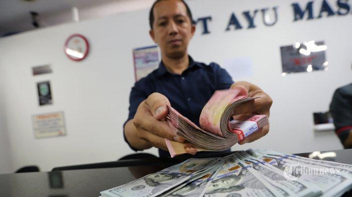 Pegawai menunjukan uang dolar Amerika Serikat dan rupiah di gerai penukaran uang Ayu Masagung di Jalan Kramat Kwitang, Senen, Jakarta Pusat, Kamis (19/3/2020). Nilai tukar rupiah terus tertekan sejak beberapa pekan terakhir, terutama setelah merebaknya wabah virus covid-19. Rupiah, kini selalu berada di atas Rp 15 ribu per dolar AS.