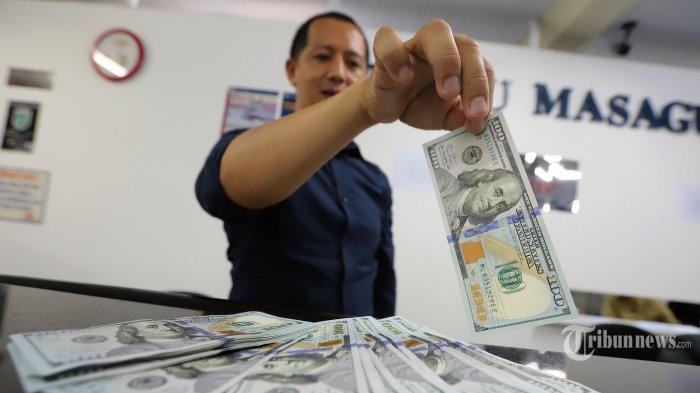 Pegawai menunjukan uang dolar Amerika Serikat di gerai penukaran uang Ayu Masagung di Jalan Kramat Kwitang, Senen, Jakarta Pusat, Kamis (19/3/2020). Nilai tukar rupiah terus tertekan sejak beberapa pekan terakhir, terutama setelah merebaknya wabah virus covid-19.