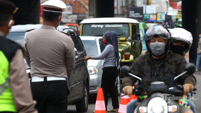 Petugas Gugus Tugas Percepatan Penanganan Virus Covid-19 Tingkat Kota Bandung menyuruh penumpang mobil pribadi yang duduk di kursi depan untuk pindah ke kursi bagian belakang di Cek Poin Pembatasan Sosial Berskala Besar (PSBB) Kota Bandung di Jalan Cibaduyut Raya, Kota Bandung, Jawa Barat, Minggu (3/5/2020). Penerapan PSBB Bandung Raya hari ke-11 di cek poin perbatasan Kota Bandung dan Kabupaten Bandung ini masih banyak yang melanggar, sehingga memaksa petugas menyuruh pengendara untuk balik arah. Tribun Jabar/Gani Kurniawan