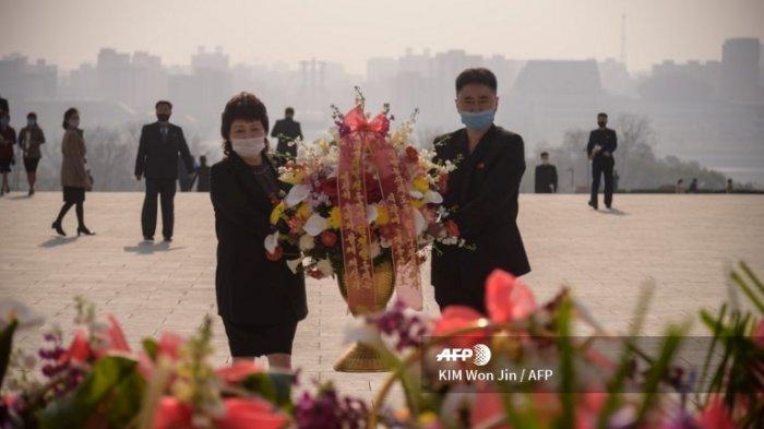 Warga memakai masker meletakkan bunga di depan patung pemimpin Korea Utara Kim Il Sung dan Kim Jong Il pada hari ulang tahun ke-108 dari pemimpin Korea Utara Kim Il Sung atau yang dikenal sebagai 'Hari Matahari' di Pyongyang, Rabu (15/4/2020).