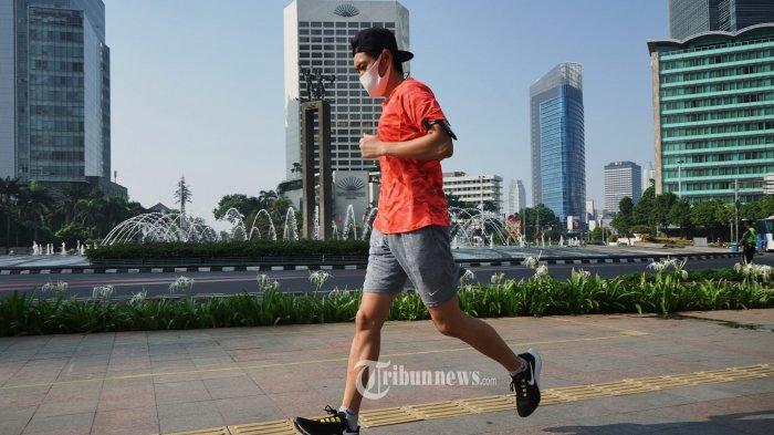 Warga masih terlihat berolahraga di sekitar bundaran HI Jakarta pada hari pertama pemberlakuan pembatasan kegiatan masyarakat (PPKM) darurat, Sabtu (3/7/2021). Sejumlah jalan di Jakarta diberlakukan penyekatan dan pembatasan kegiatan masyarakat selama masa PPKM darurat sejak 3 Juli hingga 20 Juli 2021 untuk mencegah penyebaran Covid-19. TRIBUNNEWS/HERUDIN