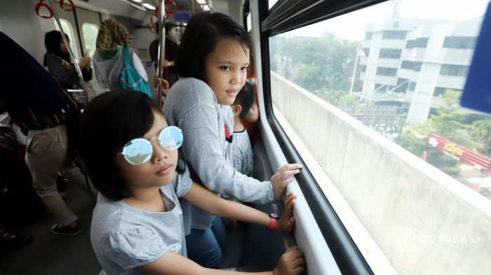 Anak-anak menikmati perjalanan uji coba kereta Light Rail Transit (LRT) Jakarta di Stasiun Velodrome, Rawamangun, Jakarta Timur, Selasa (11/6/2019). PT LRT Jakarta kembali melakukan uji coba secara gratis bagi warga yang tertarik menjajal LRT. Uji publik kali ini akan berlangsung selama 11 hari, terhitung sejak 11 Juni hingga 21 Juni 2019. Tribunnews/Jeprima