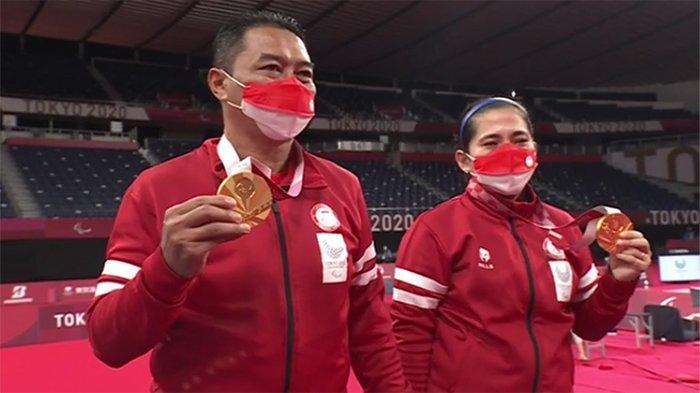 Pasangan ganda campuran bulutangkis Indonesia Harry Susanto (kiri) dan Leani Ratri Oktila (kanan) meraih medali emas di Paralimpiade Tokyo, Minggu (5/9/2021). Harry dan Leani  memegang medali emas dan buket Paralimpiade.