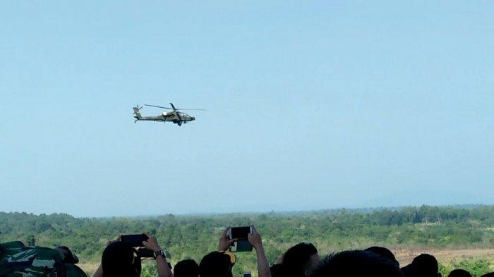 Warga mengabadikan penampakan helikopter Apache AH-64E saat menembakan sasarannya di atas area Latihan Antar Cabang TNI AD Kartika Yudha 2019 di Batu Raja, Ogan Komering Ulu, Sumatera Selatan, Senin (19/8/2019) pagi.