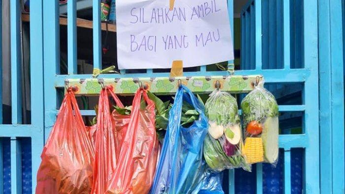 Seorang warga di Cimahi, Jawa Barat, berbagi sayuran pada warga yang membutuhkan dengan menggantungkannya di pagar rumah.