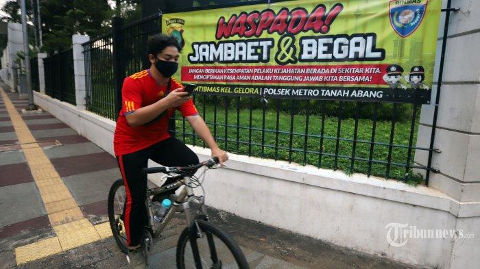 Pesepeda saat melintasi spanduk himbauan tindak kejahatan yang bertuliskan Waspada Jambret & Begal yang terpasang di kawasan Sudirman, Jakarta Pusat, Rabu (21/10/2020). Tingginya angka penjambretan terhadap pesepeda dan pejalan kaki di kawasan sudirman membuat petugas kepolisian memasang beberapa spanduk untuk memberikan himbauan kepada pada pengguna jalan. Tribunnews/Jeprima (Tribunnews/JEPRIMA)