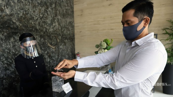 Pengunjung menggunakan hand sanitizer saat akan check in di sebuah hotel di kawasan TB Simatupang, Jakarta Selatan, Senin (8/6/2020). Secara bertahap sejumlah hotel di Jakarta mulai beroperasi kembali dengan tetap mengedepankan protokol kesehatan di tengah pandemi virus corona (Covid-19) yang belum berakhir. Tribunnews/Jeprima