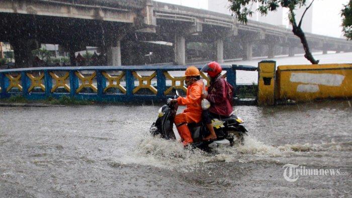 Penguna jalan melintas genangan air di perempatan Jalan Lodan Raya, Ancol, Jakarta Utara, Rabu (25/11/2020). Hujan deres membuat sejumlah titik di DKI Jakarta tergenang. (WARTAKOTA/Henry Lopulalan)