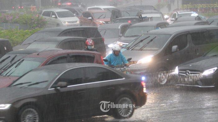 Motor tetap berjalan dibawah guyuran hujan  di sertai angin yang menguyur kawasan Bundaran HI, Menteng Jakarta Pusat, Rabu(14/4/2021).