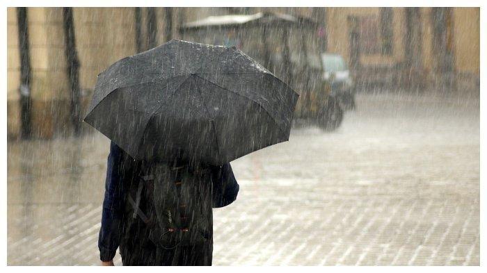 Ilustrasi seseorang memakai payung di tengah hujan. BMKG: Curah Hujan di Awal Tahun Masih Signifikan, Hujan Petir hingga Cuaca Ekstrem.