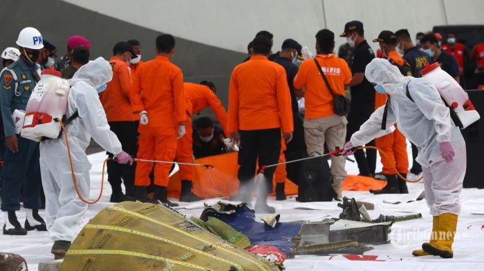 Petugas menyemprotkan cairan disinfektan ke bagian pesawat Sriwijaya Air SJ182 rute Jakarta - Pontianak yang jatuh di perairan Pulau Seribu di Dermaga JICT, Tanjung Priok, Jakarta Utara, Minggu (10/1/2021). Temuan bagian pesawat selanjutnya akan diperiksa oleh KNKT sedangkan potongan tubuh korban diserahkan kepada DVI Polri untuk identifikasi lebih lanjut. TRIBUNNEWS/IRWAN RISMAWAN