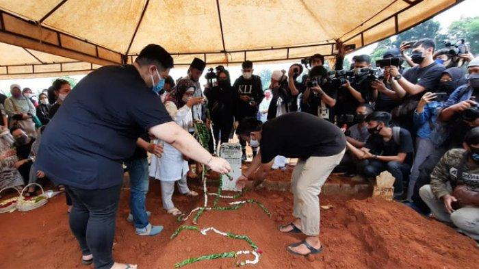 : Ivan Gunawan saat menaburkan bunga dan menyiramkan makam sang ayah di TPU Kampung Kandang, Jakarta Selatan, Senin (13/7/2020).