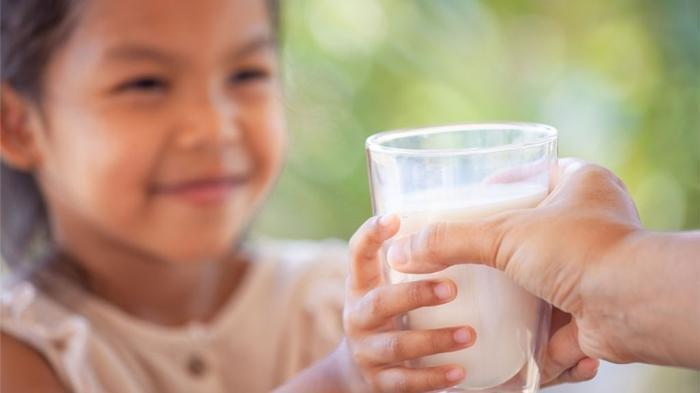 ilustrasi memberikan susu pertumbuhan sebagai pelengkap nutrisi anak.