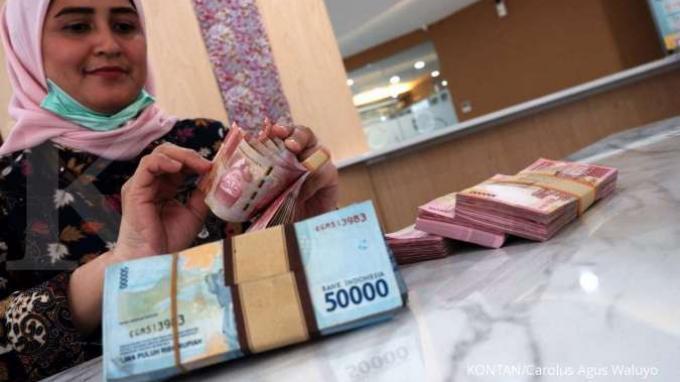 ILUSTRASI. Teller menghitung mata uang rupiah di salah satu bank di Jakarta, Selasa (7/4). Jelang siang, rupiah menguat 0,40% ke Rp 14.657 per dolar AS.