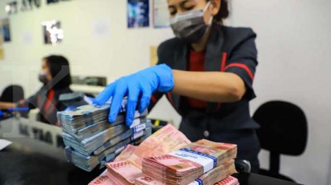 Petugas menghitung uang rupiah di money changer Ayu Masagung, Jakarta, Kamis (19/3/2020).