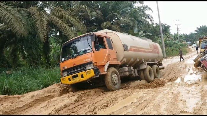 Ilustrasi truk ODOL mengangkut minyak sawit mentah (CPO) terperosok saat melintasi medan berlumpur.