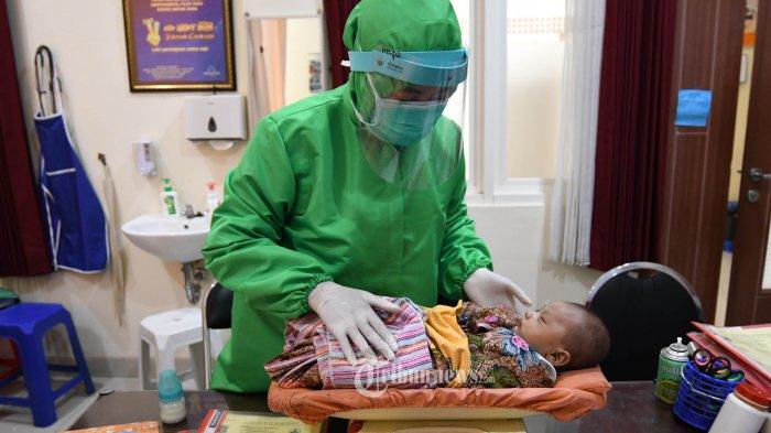 IMUNISASI ANAK - Petugas mengenakan alat pelindung diri (APD) lengkap menyuntikkan vaksin pada anak yang mengikuti program imunisasi di Puskesmas Ngagel Rejo, Selasa (30/6/2020). Pelayanan imunisasi untuk anak tetap berjalan sesuai jadwal, meski saat ini Indonesia tengah dirundung wabah COVID-19 akibat virus Corona. Pelayanan menerapkan protokol kesehatan pencegahan penularan COVID-19. SURYA/AHMAD ZAIMUL HAQ
