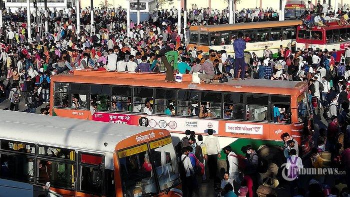 Pekerja migran India bersama keluarganya berbaris di terminal bus Anand Vihar untuk pulang ke desanya saat pemerintah memberlakukan lockdown, sebagai tindakan pencegahan atas penyebaran virus corona baru Covid-19 di New Delhi, Sabtu (28/3/2020). Pada 28 Maret 2020 puluhan ribu pekerja migran India beserta keluarganya 28 berjuang memasuki bus yang dikelola negara bagian terpadat di India, untuk membawa mereka ke kampung halaman mereka di tengah pandemi virus corona. AFP/BHUVAN BAGGA
