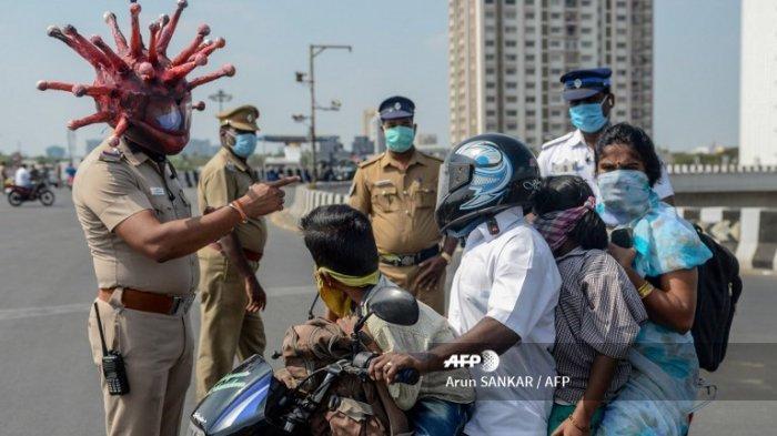 Inspektur polisi Rajesh Babu mengenakan helm bertema virus corona berbicara kepada sebuah keluarga di sebuah pos pemeriksaan selama lockdown nasional yang diberlakukan pemerintah sebagai langkah pencegahan terhadap coronavirus COVID-19 di Chennai pada 28 Maret 2020.