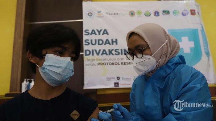 Vaksinator menyuntikkan vaksin Covid-19 kepada warga di Sentra Vaksinasi Covid-19 Ikatan Pekerja Sosial Masyarakat (IPSM) Nasional, di Gelanggang Olahraga Remaja (GOR) Rawamangun, Jakarta Timur, Kamis (16/9/2021).