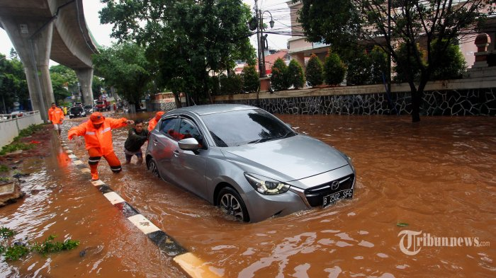 Warga mendorong mobil yang mogok di Jalan Kapten Tendean, Jakarta Selatan, karena terjebak banjir, Rabu (1/1/2019). Banjir merendam beberapa wilayah di Ibu Kota Jakarta dan sekitarnya, akibat hujan deras sejak malam pergantian tahun. TRIBUNNEWS/DANY PERMANA