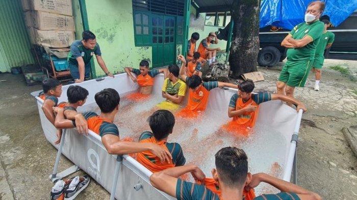 BERENDAM AIR ES- Para pemain sepak bola tim Jawa Timur berendam air es setelah mereka menang atas Jawa Barat.
