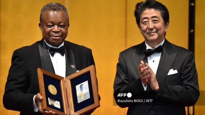 Jean-Jacques Muyembe-Tamfum dari Kongo (Kiri) berpose dengan Perdana Menteri Jepang Shinzo Abe (Kanan) setelah menerima Penghargaan Ketiga Hideyo Noguchi Afrika dalam kategori penelitian medis pada upacara penghargaan di Tokyo pada 30 Agustus 2019 di sela-sela acara Konferensi Internasional Tokyo tentang Pembangunan Afrika (TICAD).